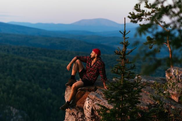 Um viajante está sentado na beira de um penhasco com vista para a floresta do alto do vôo. viajar como forma de vida, aventura, férias. um viajante ao pôr do sol nas montanhas. copie o espaço