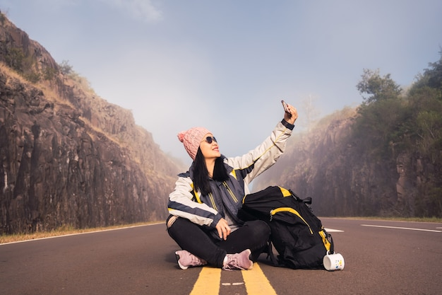 Um viajante feliz e sorridente tira uma selfie no meio da estrada.