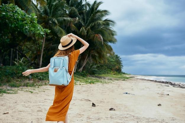 Um viajante feliz na ilha segura um chapéu na cabeça e uma mochila