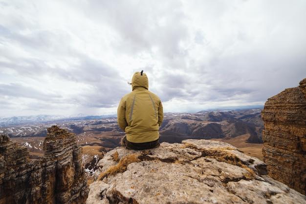 Um viajante masculino com paletó senta-se à beira de um penhasco e aprecia a natureza da montanha