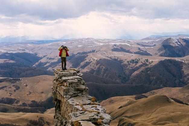 Um viajante masculino com paletó viaja pelas montanhas, aprecia a natureza e o ar puro