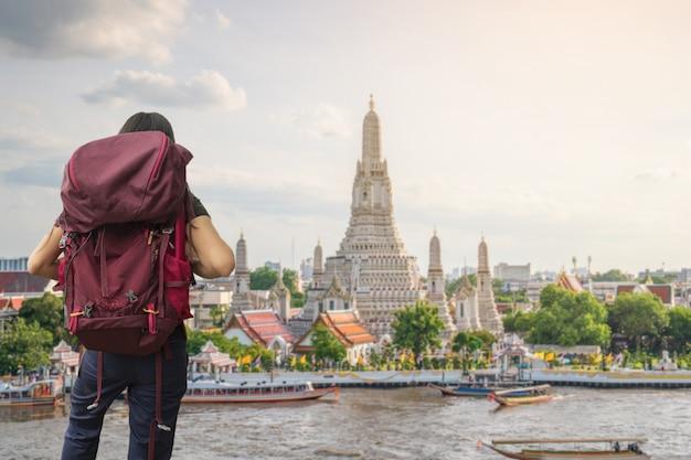 Um viajante que viaja no templo de wat arun ratchawararam ratchawaramahawihan em banguecoque, tailândia