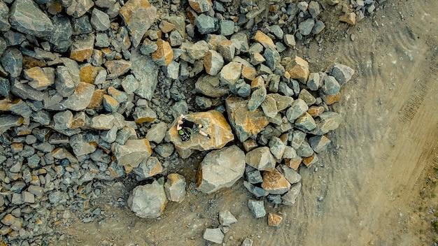 Um viajante se deita em uma grande pedra cercada por muitas pedras no verão. um, homem, com, um, mochila, descansar
