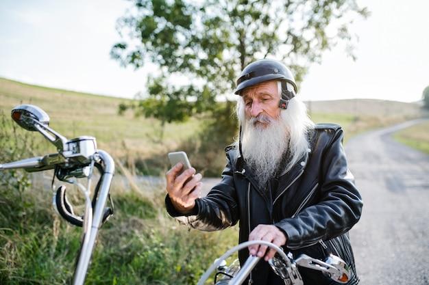 Um viajante sênior com moto na zona rural, tomando selfie com smartphone.
