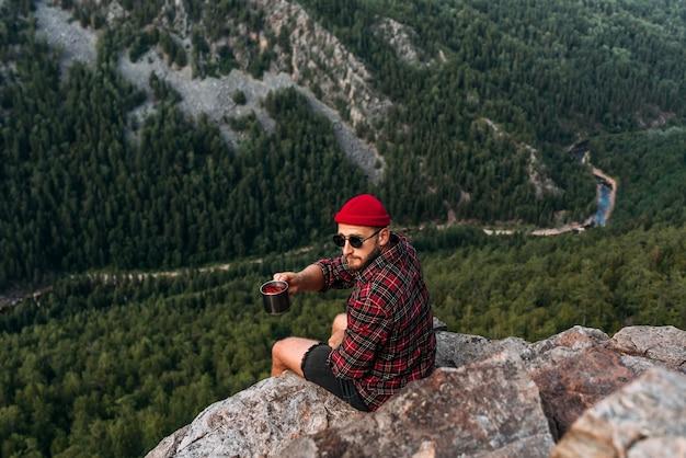 Um viajante sentado à beira de um penhasco. um viajante está sentado em uma rocha com uma vista panorâmica da floresta. o conceito de recreação e turismo. um homem desfruta de belas vistas. viajar por