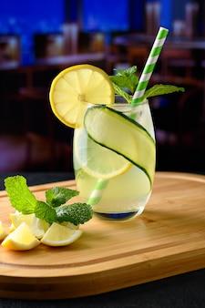 Um vidro com uma bebida de limão siciliano na imagem borrada de fundo de um ambiente de bar noturno