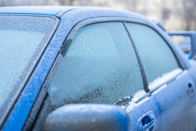 Um vidro de janela de carro sob o gelo congelado, conceito de problemas de inverno frio