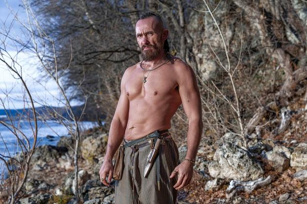 Um viking barbudo com o torso nu e a cabeça raspada está de pé na margem do rio