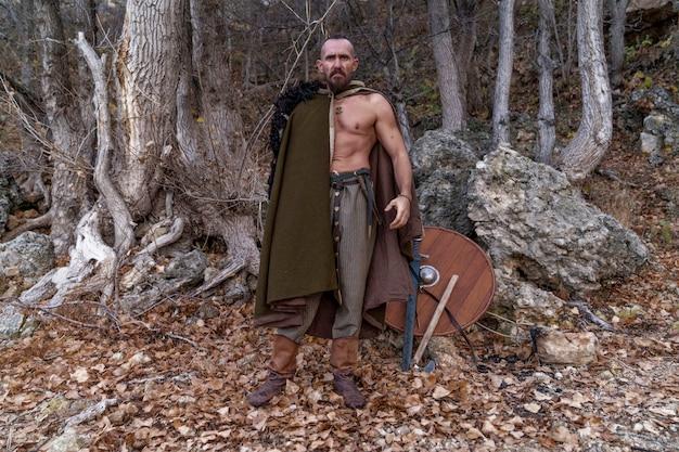 Um viking barbudo com uma pele de animal jogada sobre os ombros está de pé ao pé de uma montanha entre as árvores
