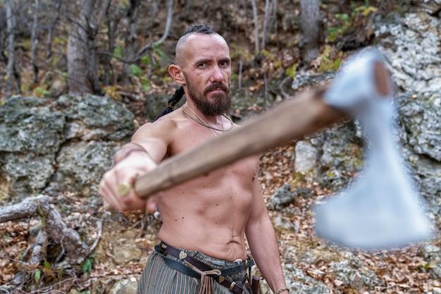 Um viking barbudo com uma trança na cabeça está de pé no sopé da montanha e segura um machado nas mãos