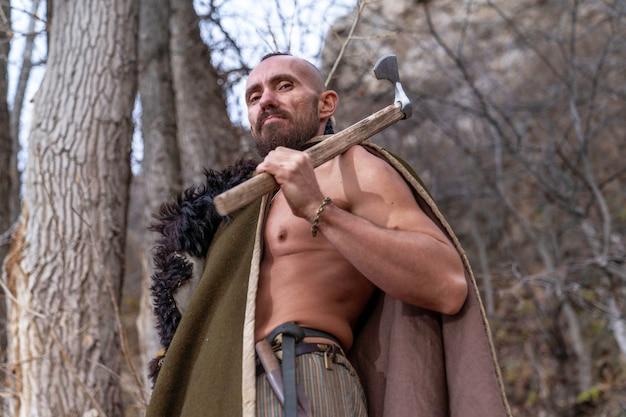 Um viking barbudo está entre as árvores vestido com a pele de um animal e segura um machado de batalha na mão