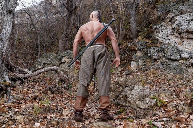 Um viking nu com uma espada embainhada pendurada nas costas está de pé no sopé da montanha