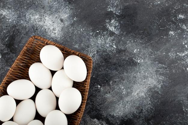 Um vime de madeira cheio de ovos de galinha crus.