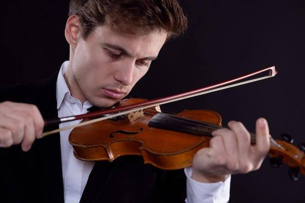 Um violinista toca violino em um concerto da orquestra sinfônica