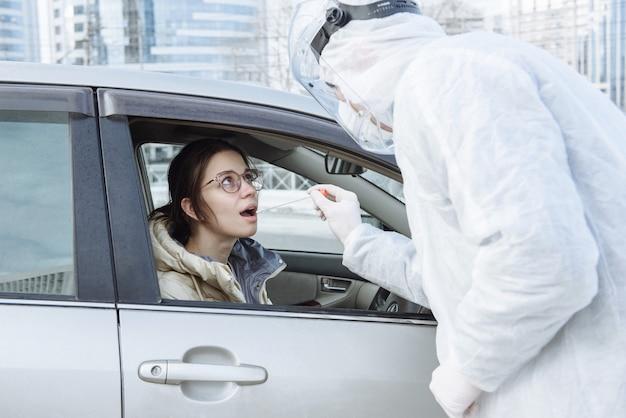 Um virologista em um traje de proteção de epi, máscara, luvas faz um esfregaço ou teste com um cotonete para coronavírus covid-19 para um motorista de carro
