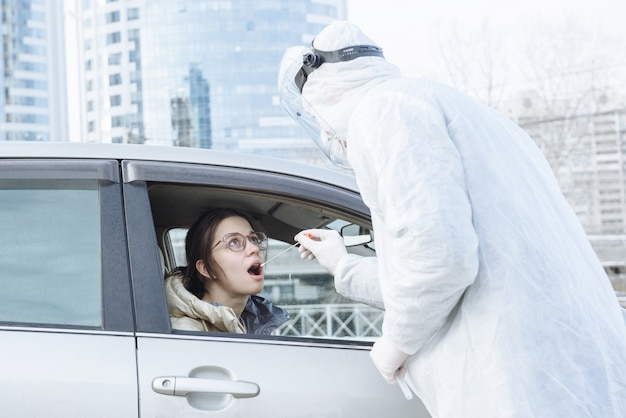 Um virologista ou médico usando roupas de proteção anti-perigo (epi) coleta uma amostra de um teste de pcr com um cotonete
