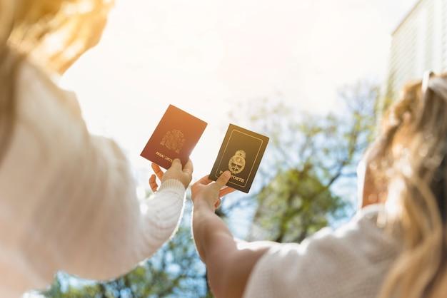 Um, visão aérea, de, dois, femininas, turista, levantamento, seu, braços, mostrando, seu, passaporte, contra, céu