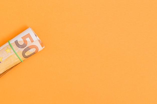 Um, visão aérea, de, enrolado, nota euro, amarrada, com, borracha, ligado, um, laranja, fundo