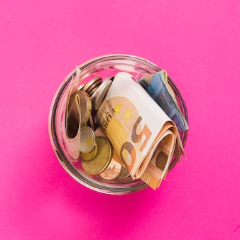 Um, visão aérea, de, euro notas, e, moedas, em, jarro vidro aberto, contra, fundo cor-de-rosa