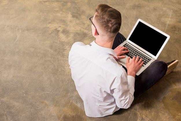 Um, visão aérea, de, homem jovem, sentar chão concreto, usando computador portátil