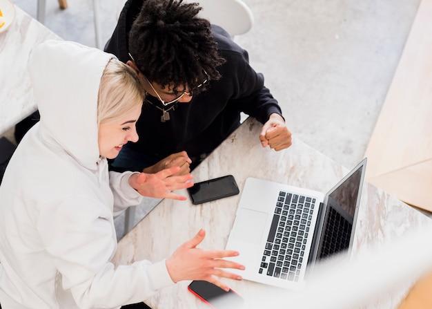 Um, visão aérea, de, interracial, par jovem, alegrando, após, olhar, laptop, ligado, tabela