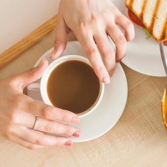 Um, visão aérea, de, mão mulher, segurando, xícara chá, ligado, bandeja madeira