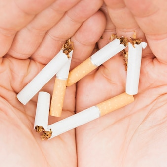 Um, visão aérea, de, mãos, segurando, cigarros quebrados