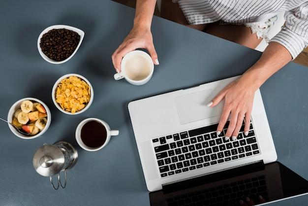 Um, visão aérea, de, mulher, com, saudável, pequeno almoço, usando computador portátil