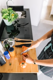 Um, visão aérea, de, mulher, corte, fatias tomate, ligado, contador cozinha