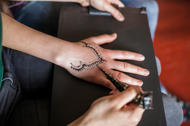 Um, visão aérea, de, mulher, fazer, heena, tatuagem, de, femininas, artista