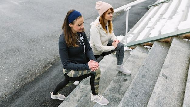 Um, visão aérea, de, mulheres jovens, esticar, seu, pernas, ligado, escadaria