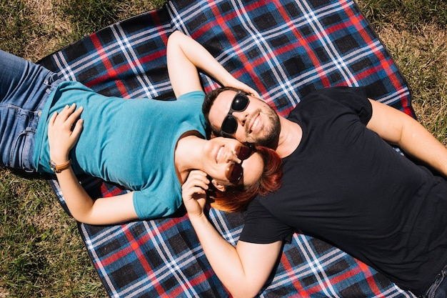 Um, visão aérea, de, par jovem, óculos sol cansativo, mentindo, ligado, cobertor