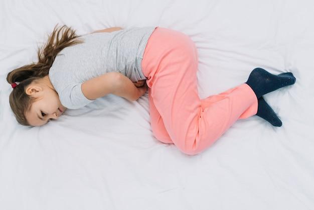 Um, visão aérea, de, um, menina, encontrar-se cama, sofrimento, de, dor estômago