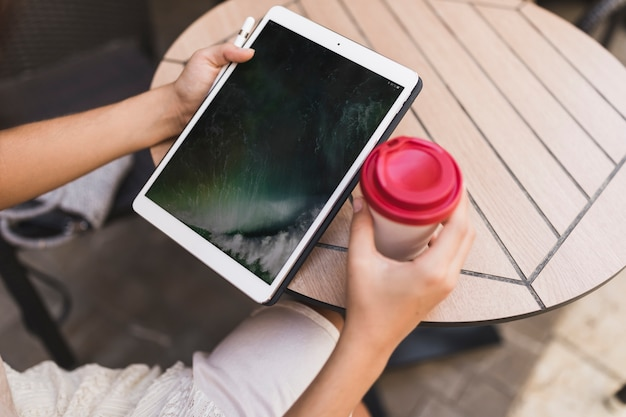 Um, visão aérea, de, um, menina, segurando, tablete digital, e, takeaway, xícara café, ligado, tabela