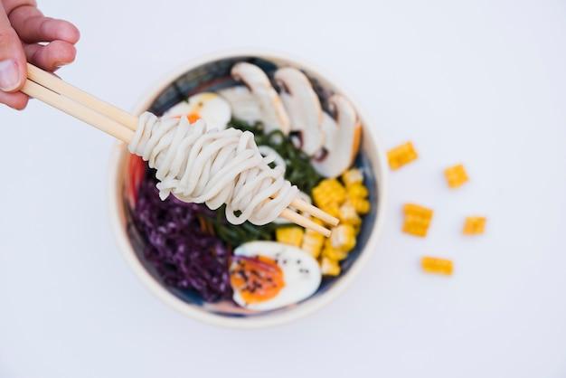 Um, visão aérea, de, um, passe segurar, noodles, com, chopsticks, sobre, a, tigela, branco, fundo