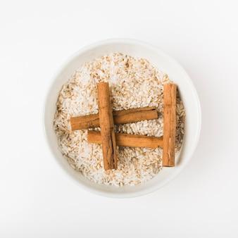 Um, visão aérea, de, varas canela, com, cru, tigela arroz, contra, fundo madeira