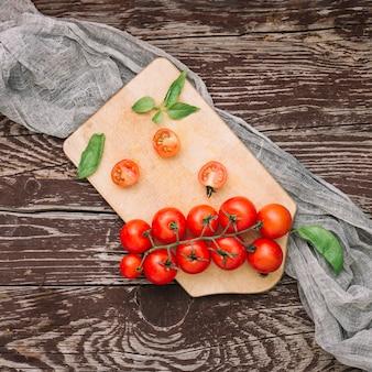 Um, visão aérea, de, vermelho, grupo, de, tomates cereja, e, manjericão, ligado, tábua cortante, sobre, a, escrivaninha madeira