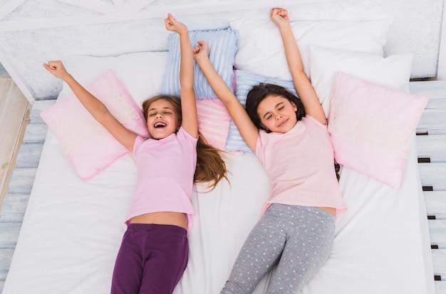 Um, vista elevada, de, duas meninas, esticar, seu, braços, enquanto, acordar cama