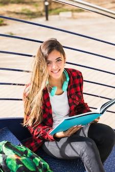 Um, vista elevada, de, estudante universidade, sentando escadaria, segurando, livro, em, mão