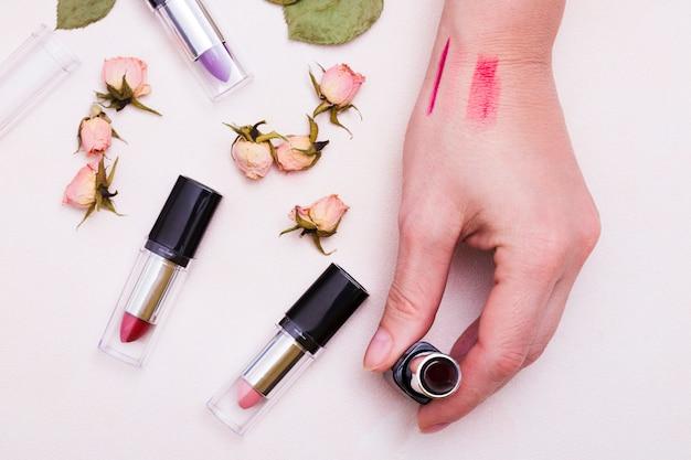 Um, vista elevada, de, mão feminina, segurando, batom, com, secado, cor-de-rosa, rosa, brotos, branco, fundo