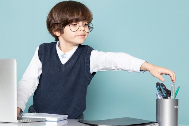 Um, vista frontal, cute, menino negócio, em, azul clássico, jamper, posando, frente, prata, laptop, trabalhando, negócio, trabalho, moda