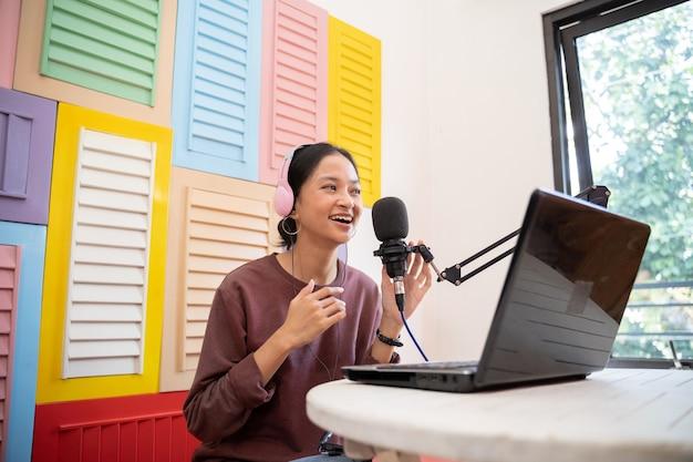 Um vlogger asiático está gravando um podcast com um microfone e um laptop