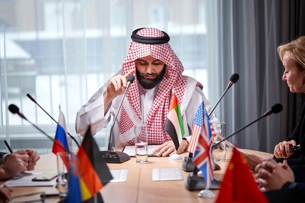 Um xeque árabe apresentando suas ideias a diversos colegas multiétnicos e ouvindo ideias para investimentos de sucesso em um escritório moderno e luminoso, use um microfone. encontro sem laços