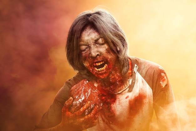 Um zumbi assustador com sangue e ferida em seu corpo come a carne crua com fundo dramático