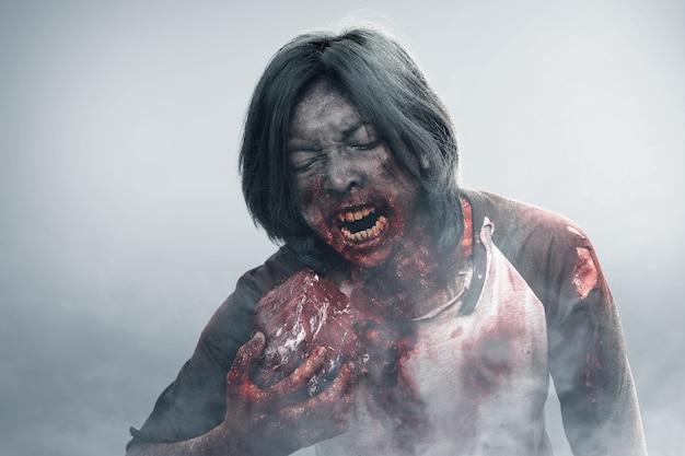 Um zumbi assustador com sangue e ferida em seu corpo come a carne crua no meio do nevoeiro