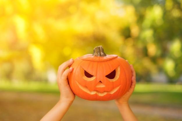 Uma abóbora com um sorriso sinistro de lanterna jacko nas mãos no halloween