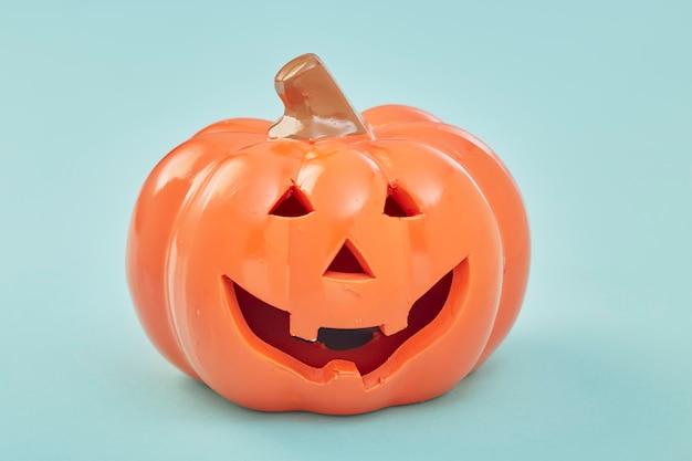 Uma abóbora de halloween no fundo azul pastel