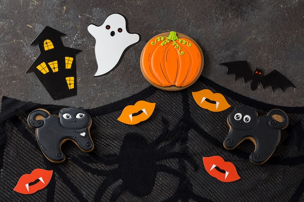 Uma abóbora em um chapéu, dois fantasmas brancos, uma teia de aranha, morcegos, lábios com dentes de um vampiro