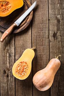 Uma abóbora fatiada em um fundo de ardósia e bancada de madeira. em uma placa com uma faca