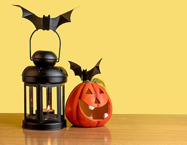 Uma abóbora laranja e uma lanterna preta ficam sobre uma mesa com um fundo amarelo. há um morcego preto na lanterna e na abóbora.